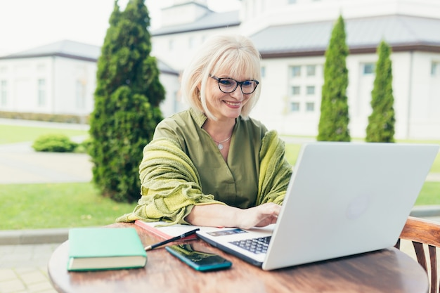 Senior beautiful business woman sitting on a chair and making notes in a notebook, with a phone and laptop in the yard