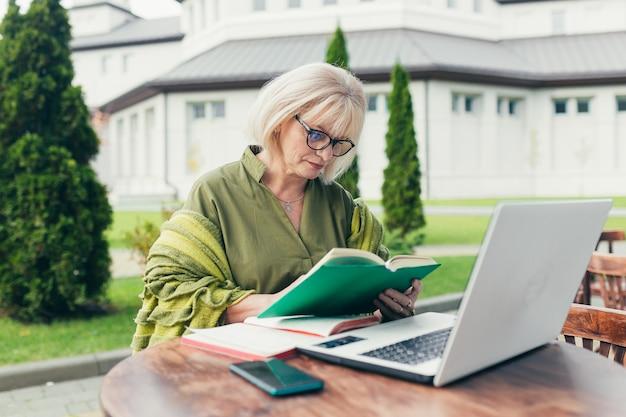 수석 아름다운 비즈니스 여자가 의자에 앉아 전화로 노트북에 메모를 만들고