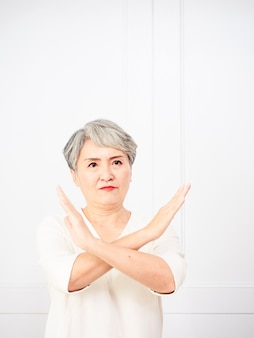 Старшая красивая седая женщина в повседневном платье делает знак остановки ладонью. предупреждающее выражение с негативным и серьезным жестом на лице.