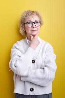 質問について非常に混乱した考えを考えている深刻な顔をしている年配の美しい白髪の女性