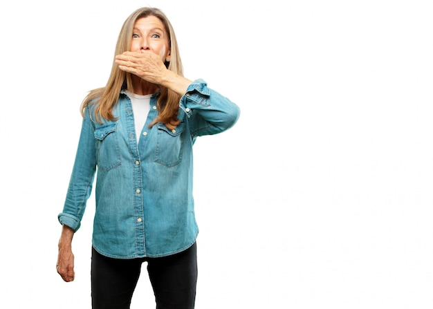 Senior beautiful woman covering mouth with hand with a gesture of surprise, in order to remain silen