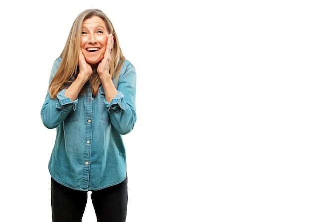 幸せな驚くべき表現を持つシニア美しい女性、目を大きく開いて広い笑顔、ファグを持つ