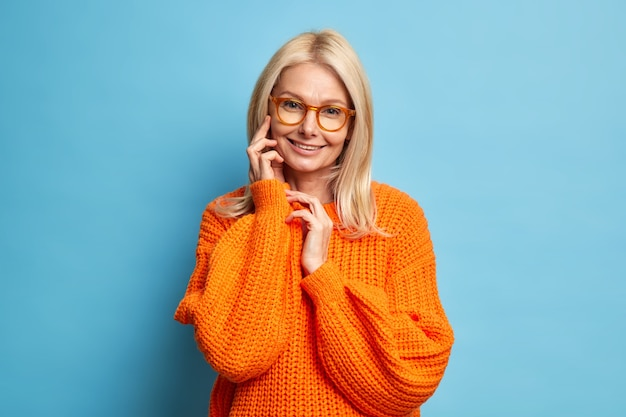 Senior beautiful woman with blonde hair healthy skin touches face gently smiles tenderly wears orange knitted sweater model
