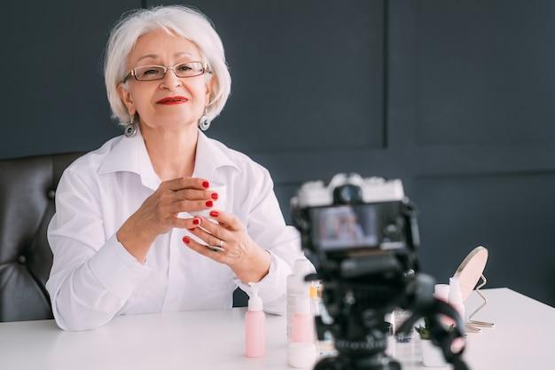수석 뷰티 블로거. 비디오 리뷰를 만드는 노인 여성