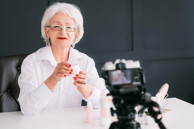 Старший блогер о бьюти-стиле. успешная деловая женщина. стильная пожилая дама делает видеоурок.
