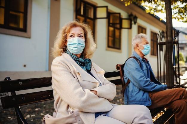 Старшая белокурая женщина в пальто и с защитной маской на сидении на скамейке со скрещенными руками.