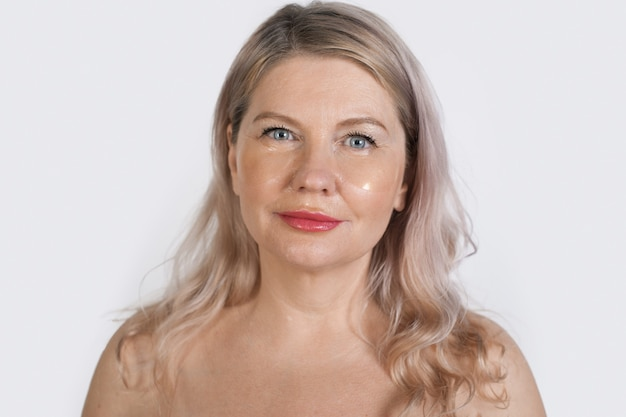 シニアブロンドの女性は裸の肩でカメラにポーズをとって透明な眼帯を着ています