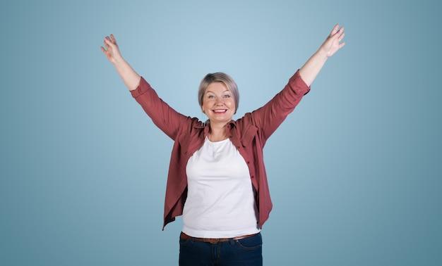手を上げてポーズをとって、青いスタジオの壁に歯を見せるシニアブロンドの女性