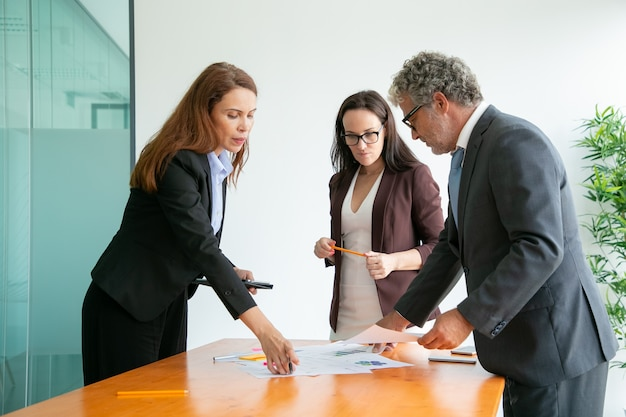 Старший босс в очках обсуждает с помощницами и рассматривает документы