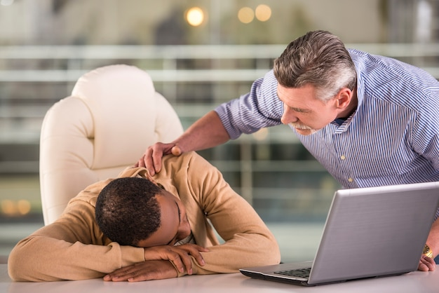 Senior boss waking sleeping young african worker in office.