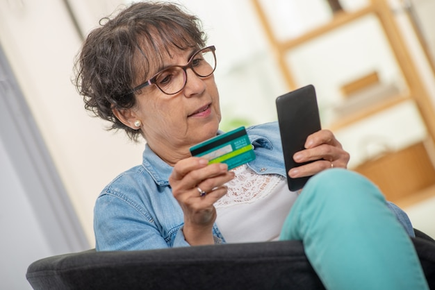Senior brunette woman shopping with smartphone and internet