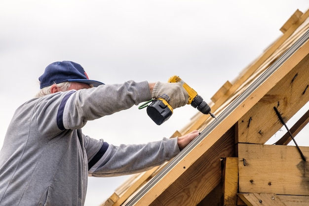 Старший строитель мужчина с отверткой привинчивает кровельный лист к крыше