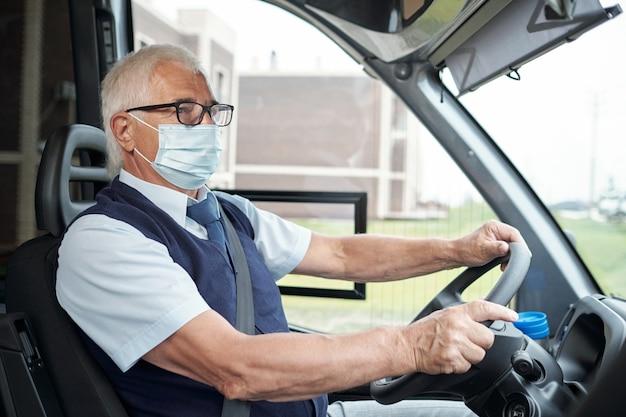 Старший водитель автобуса в очках повседневной одежды и защитной маске