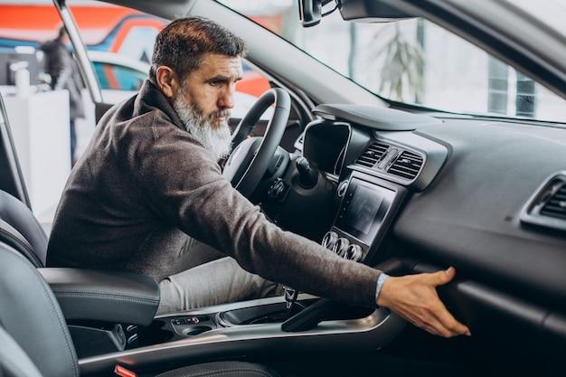 Uomo d'affari senior che sceglie un'auto nell'autosalone