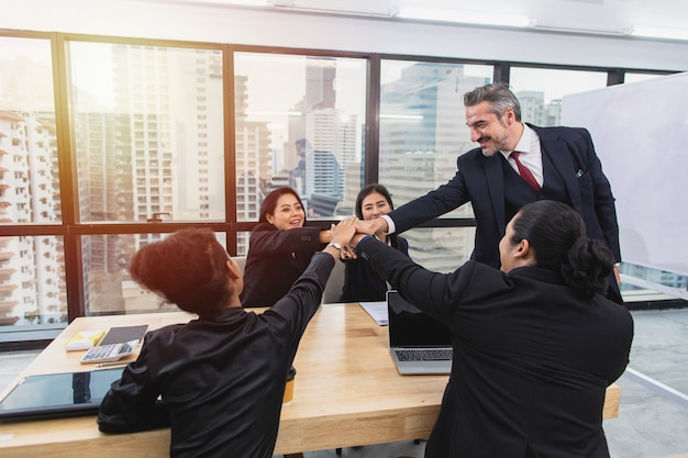 Senior business man give high five with asian colleague in meeting room at office after finish presentation for new business
