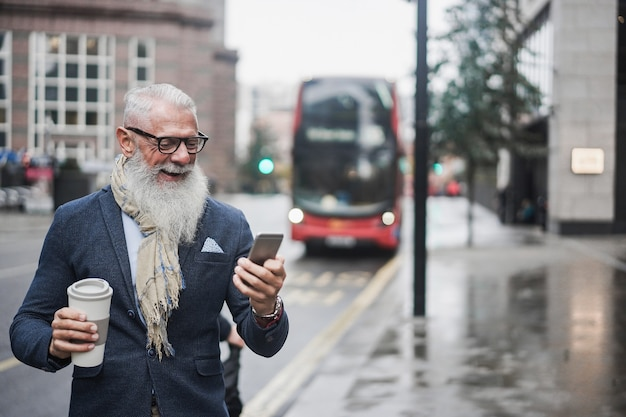 런던 버스 정류장을 배경으로 커피를 마시며 일할 수석 사업가 - 얼굴에 집중