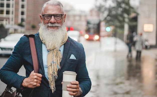 仕事に行くシニアビジネスの男性-バスを待っている間コーヒーを飲んで流行に敏感な起業家-仕事、リーダーシップ、ファッション、自信のあるコンセプト-顔に焦点を当てる