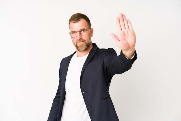 一時停止の標識を示す差し出された手で立っている白い壁に分離されたシニアビジネスの男性は、あなたを防ぎます。