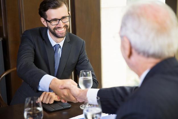 別のビジネスマンからのハンドシェイクを受けシニアビジネスマン