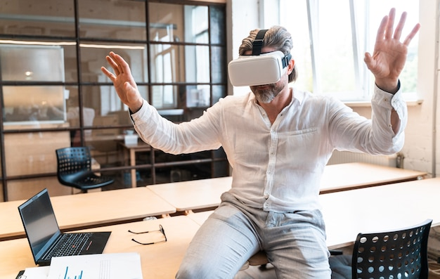 Senior business man sitting in his office and using mixed reality to develop a new project