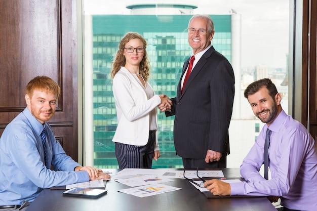 Uomo maggiore di affari che sorride mentre stringe la mano a una donna