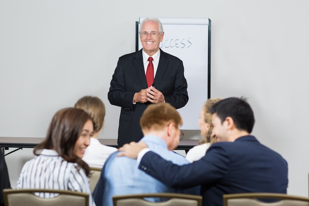 Senior business man smiling with a white chalkboard behind