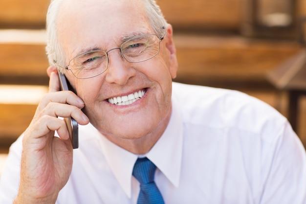 シニアビジネスマン電話で話すと笑顔