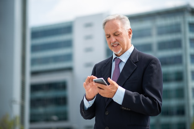 Senior business man using his smartphone outdoors