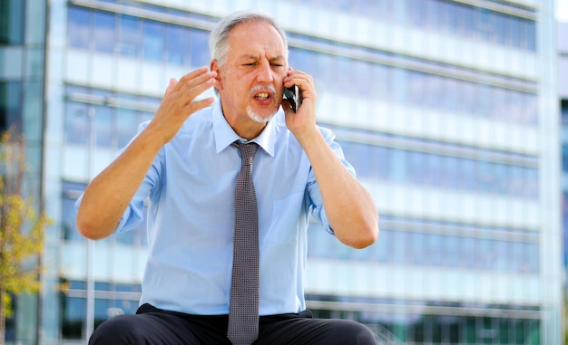 Senior business man yelling at the phone outdoor, sitting on a bench
