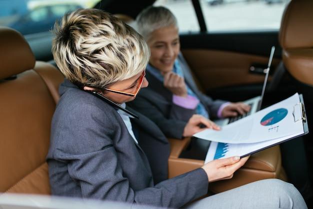 고위 비즈니스 우먼과 그녀의 조수가 리무진에 앉아 이야기하고 일하고 있습니다.