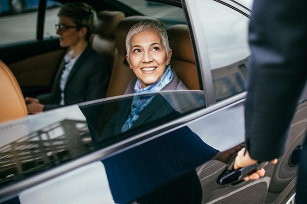 Старшая деловая женщина и ее помощник, сидя в лимузине, разговаривают и работают.