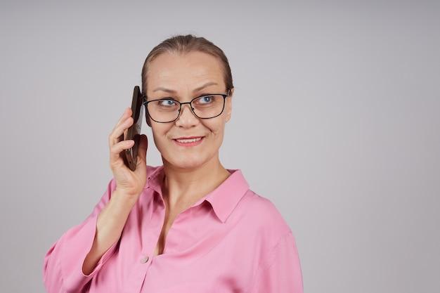 안경, 휴대 전화에 대 한 얘기는 핑크 블라우스에 수석 비즈니스 여자. 회색 배경에 고립 된 사진입니다.