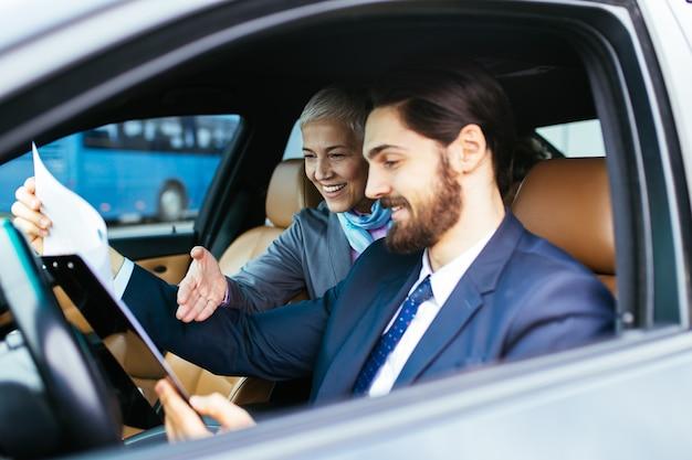 리무진에 앉아서 그녀의 운전사와 이야기하는 수석 비즈니스 우먼. 비즈니스 개념입니다.