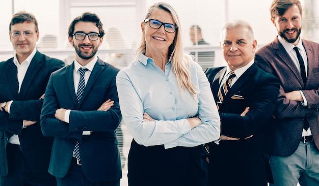 Старшая деловая женщина, стоящая перед бизнес-командой. фото с копией пространства