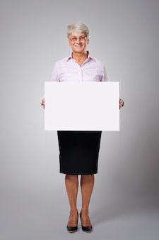 Senior business woman with empty whiteboard