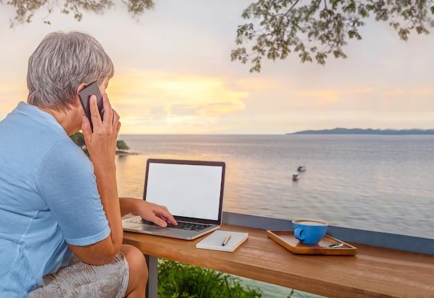 Старшая деловая женщина с ноутбуком и чашкой кофе за столиком в кафе с видом на море разговаривает по телефону