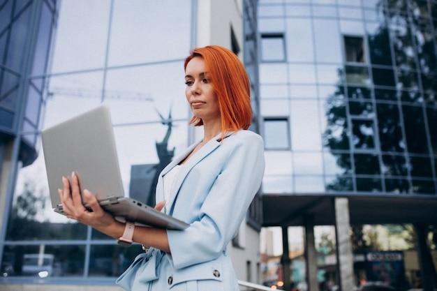 オフィスセンターでラップトップを持つシニアビジネス女性