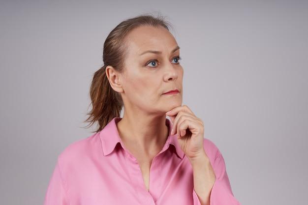 심각한 표정으로 핑크 블라우스에 포니 테일 헤어 스타일으로 수석 비즈니스 여자. 회색 배경에 고립 된 사진입니다.