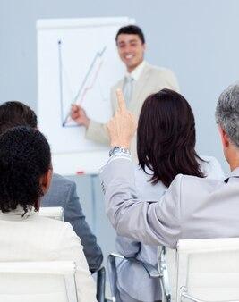 Senior businessman asking a question at a presentation