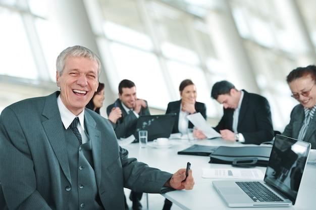 Старший бизнесмен на встрече. группа коллег в фоновом режиме