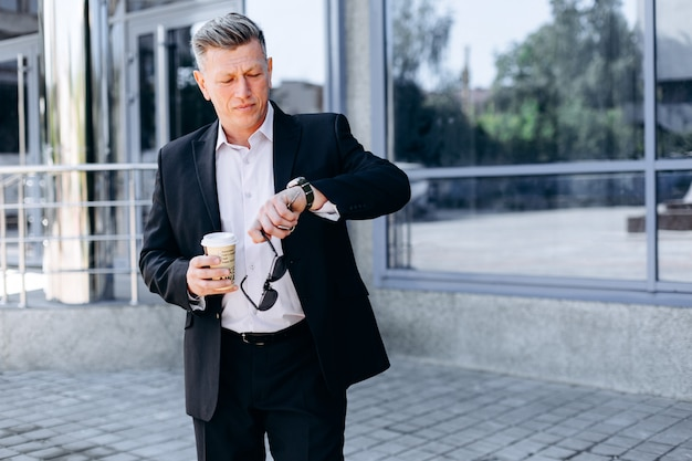 Senior businessman checking time on watch on his hand in city, holding a sunglasses and coffe glass