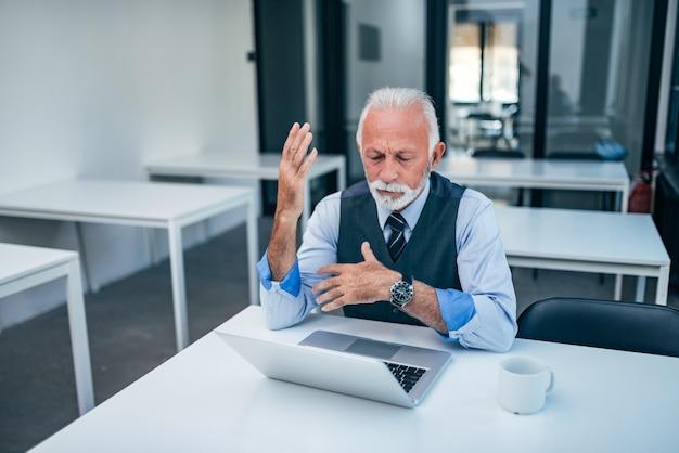 Senior businessman discussing work online.