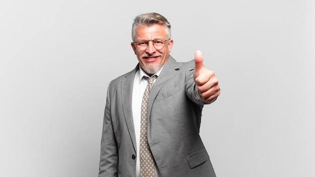 Старший бизнесмен чувствует себя гордым, беззаботным, уверенным и счастливым, позитивно улыбается и показывает палец вверх