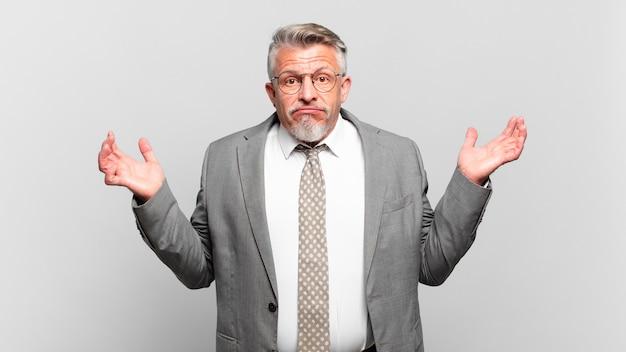 Старший бизнесмен чувствует себя озадаченным и сбитым с толку, сомневается, взвешивает или выбирает разные варианты с забавным выражением лица