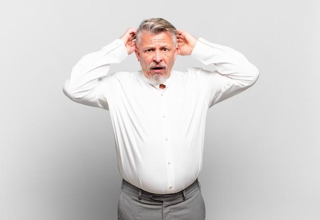ストレス、心配、不安、または恐怖を感じ、頭に手を置いて、間違ってパニックに陥るシニアビジネスマン