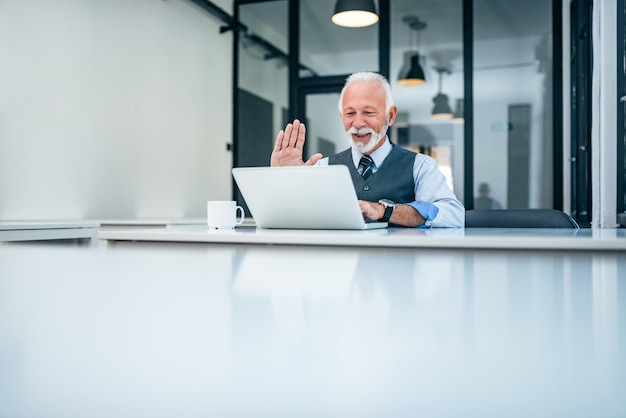 Senior businessman having video call on laptop. copy space.