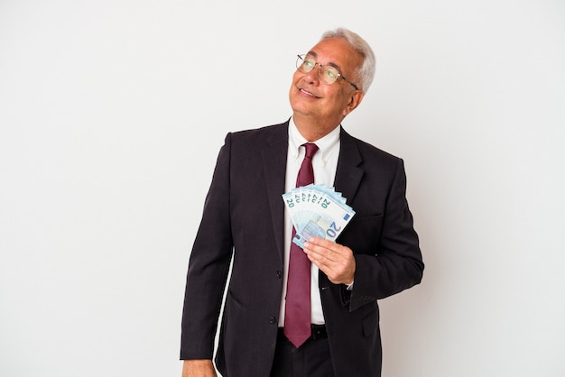 Senior businessman holding bills isolated dreaming of achieving goals and purposes