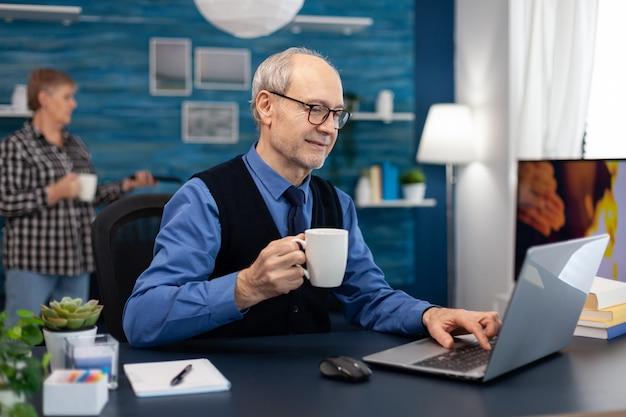 Uomo d'affari senior che tiene tazza di caffè che lavora al computer portatile