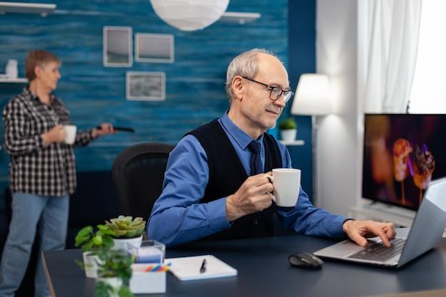ラップトップに取り組んでコーヒーのカップを保持しているシニアビジネスマン。妻がテレビのリモートを保持している間、机に座ってポータブルコンピュータを使用して自宅の職場で老人起業家。
