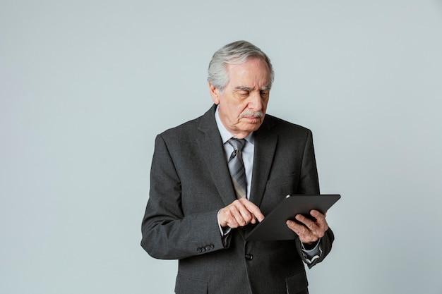 디지털 태블릿을 사용하여 정장을 입은 수석 사업가